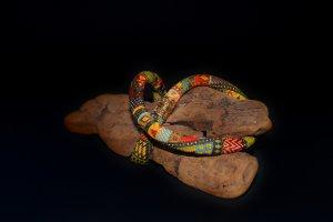 Bunte Perlenkette auf einem alten Stück Holz vor dunklem Hintergrund