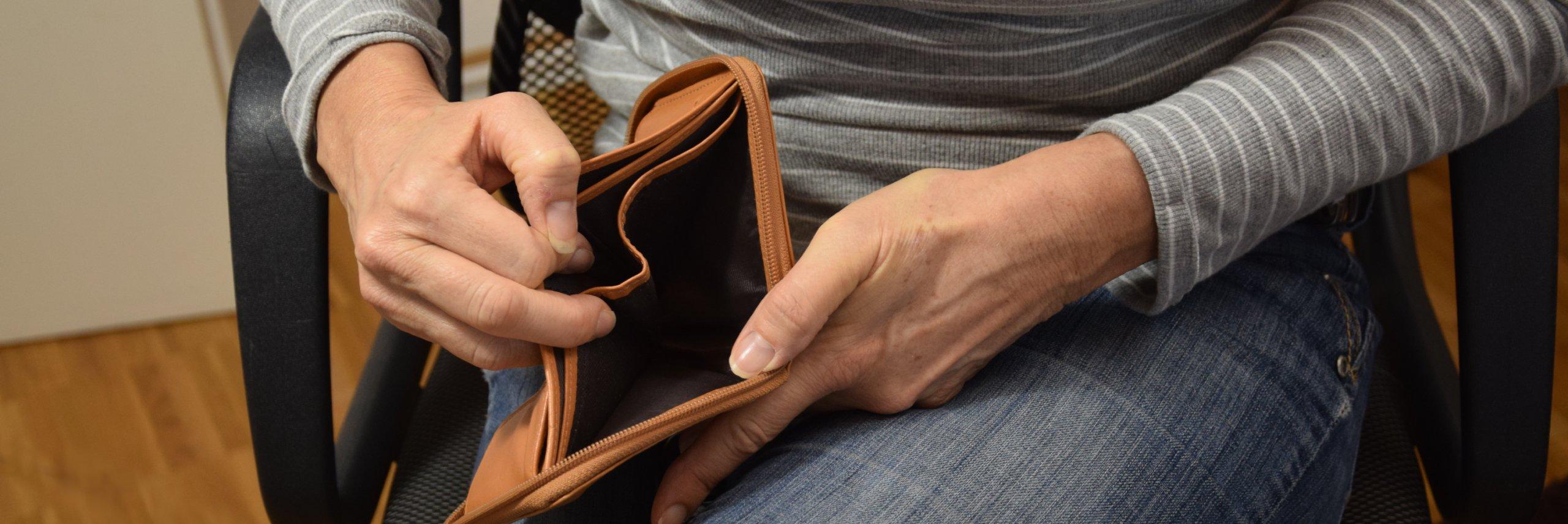 Person öffnet eine Leere Geldbörse