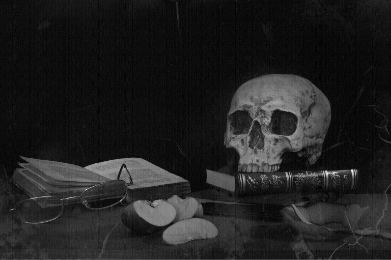 Schädel, Bücher und Äpfel auf einem Tisch