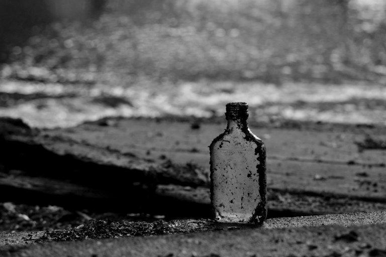 alte Schnapsflasche am Ufer eines Flusses
